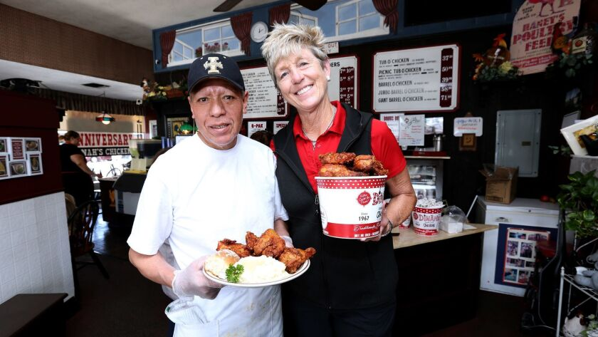 Dinah's Chicken co-owner Linda Pearson, right, with cook Leandro Rosales, at the establishment on San Fernando Road in Glendale on Friday. Dinah's has been open for 51 years and Rosales has been working there for 37 of those years.