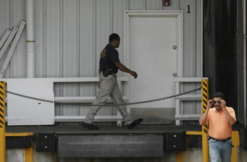 Un agente del Servicio de Inmigración y Aduanas (ICE) se dirige al interior de una fábrica donde fueron arrestadas 680 personas que trabajaban sin documentos. EFE/Aaron Sprecher/Archivo