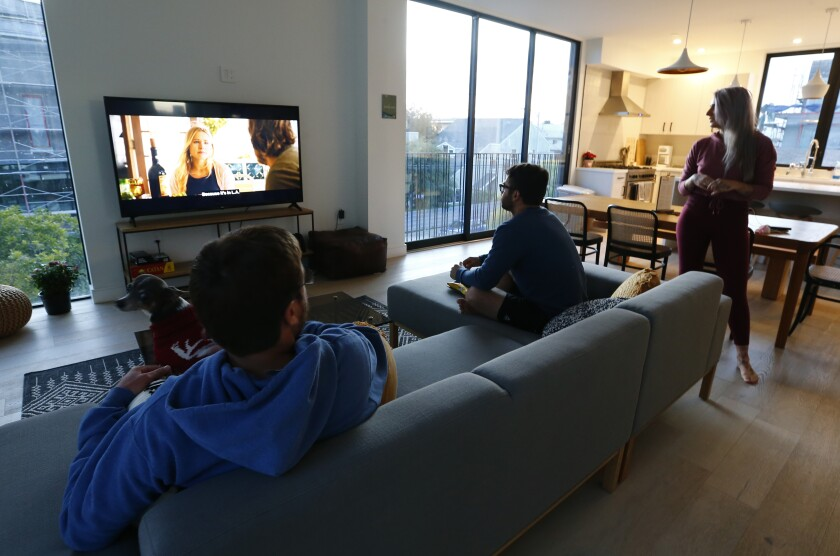 From left, Colin Huitfeldt, Jake Viramontez-Smith and Julia O. Test, watch television in their shared-living apartment building in Venice.