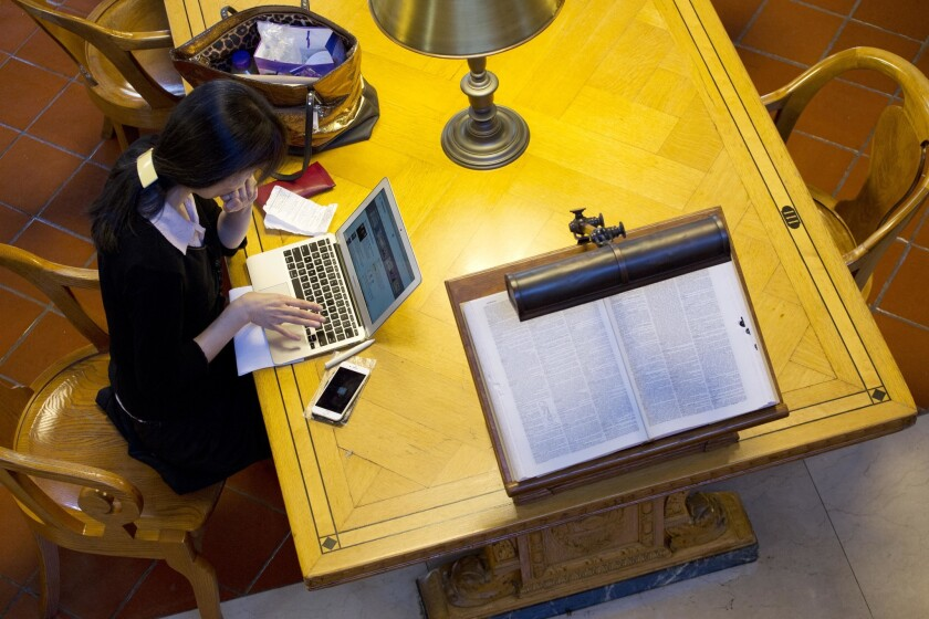 A woman works on her laptop in the Rose Main Reading Room of the New York Public Library this month.