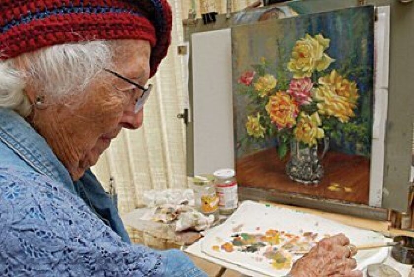 Artist Lillis Lewis poses at her work station in her home studio. Courtesy photos