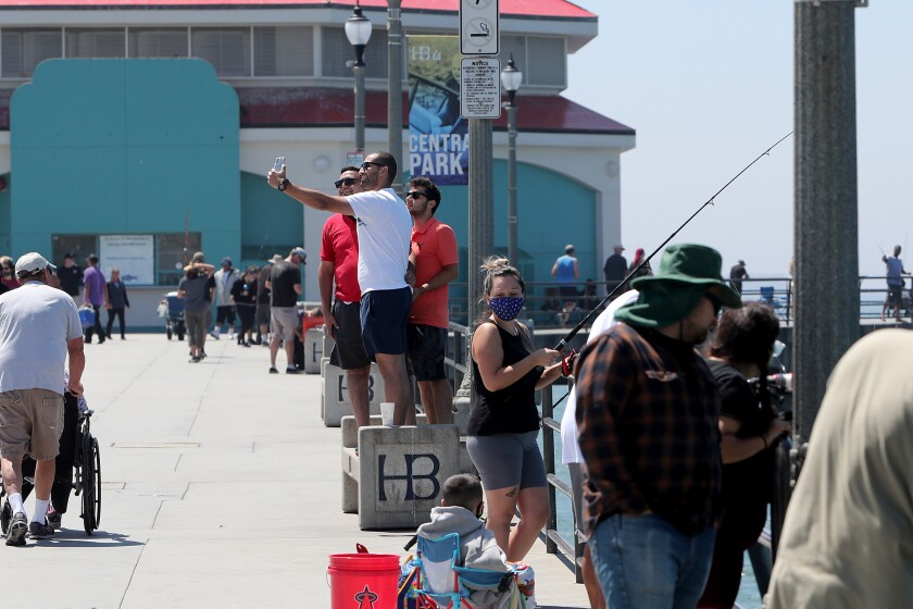 Visitors stand on a bench for an elevated picture at Huntington Beach Pier.