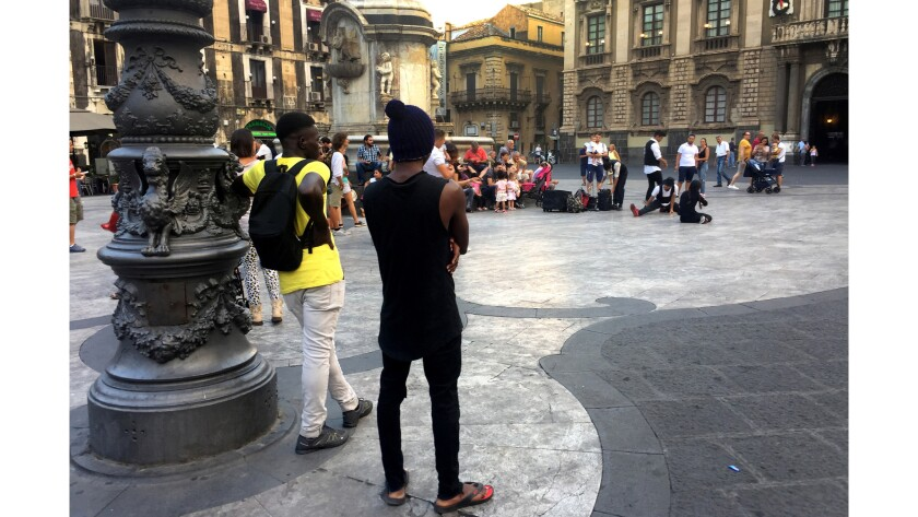 Two young migrants watch street performers in Catania's Piazza del Duomo.