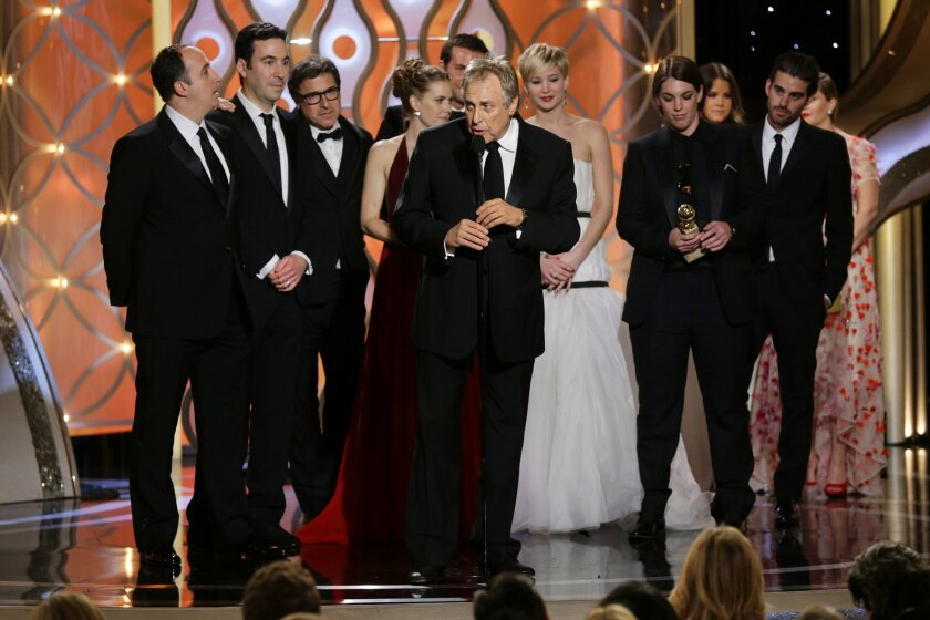 """This image released by NBC shows Charles Roven, center, accepting the award for best motion picture comedy for """"American Hustle"""" during the 71st annual Golden Globe Awards at the Beverly Hilton Hotel on Sunday, Jan. 12, 2014, in Beverly Hills, Calif. (AP Photo/NBC, Paul Drinkwater)"""