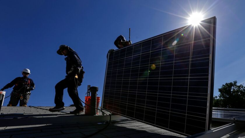 Workers install solar panels on a roof. Lawmakers this week approved more consumer protections for PACE loans, which pay for energy-efficient home improvements, after some borrowers said they didn't understand what they were getting into.