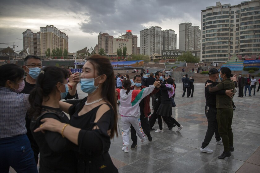 People dance to music at a public square in Aksu in western China's Xinjiang Uyghur Autonomous Region, as seen during a government organized trip for foreign journalists, Tuesday, April 20, 2021. (AP Photo/Mark Schiefelbein)