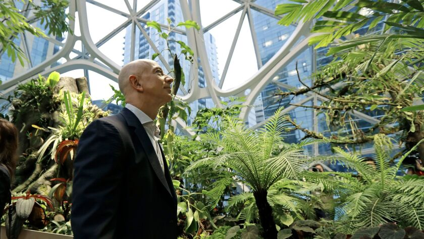 Amazon Chief Executive Jeff Bezos walks through Amazon Spheres, three plant-filed geodesic domes that serve as a work and gathering place for Amazon employees in Seattle.