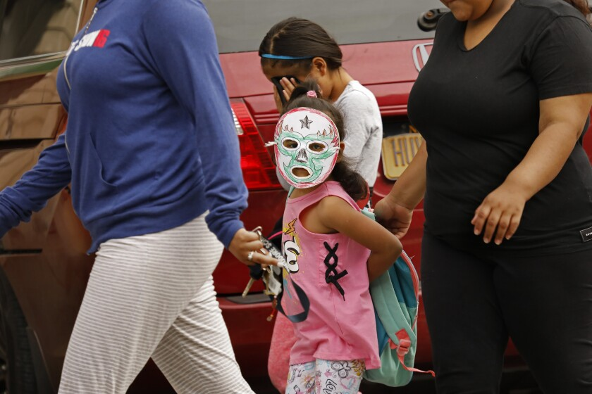 Children, including a girl wearing a mask to protect her identity, are taken to Cayuga Center in East Harlem, New York City. Hundreds of migrant children separated from their parents by federal immigration officials are being cared for at the facility.