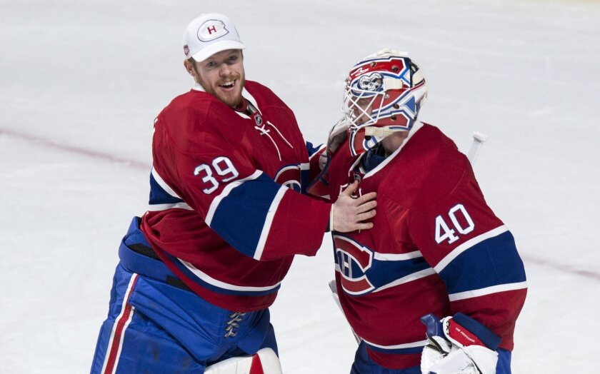 Montreal Canadiens goalie Ben Scrivens (40) is congratulated by fellow goaltender Mike Condon following the team's 4-2 victory over the Tampa Bay Lightning in an NHL hockey game, Tuesday, Feb. 9, 2016, in Montreal.  (Paul Chiasson/The Canadian Press via AP) MANDATORY CREDIT