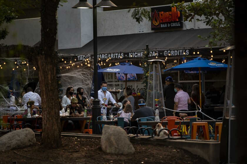 Diners sit outdoors at the Fire Up Bar & Grill in Riverside.