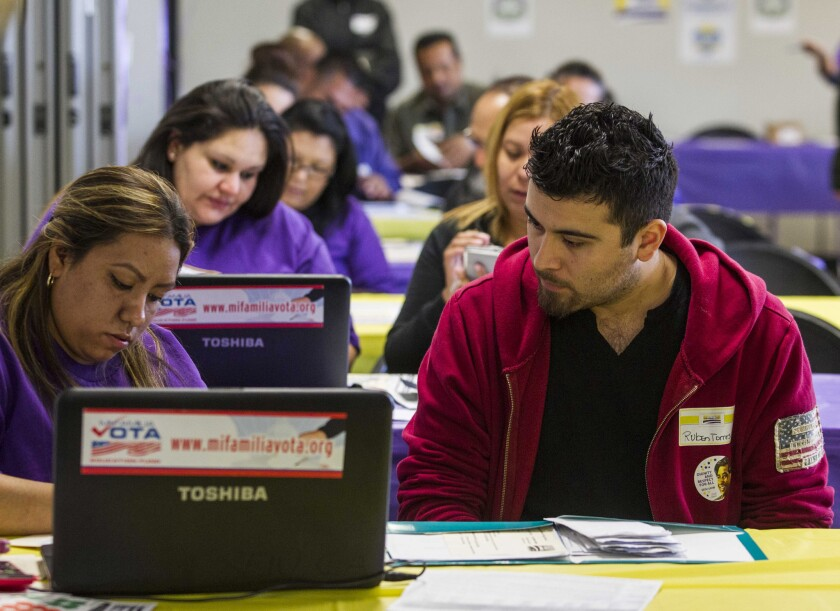 Kathy Santana, left , assists Ruben Torres, 27, during a March 31 healthcare enrollment event in Commerce, Calif.
