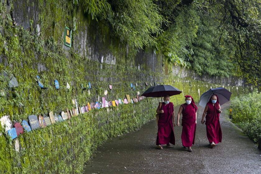 Exile Tibetan Buddhist nuns wearing face masks as a precaution against the coronavirus circumambulate the residence of their spiritual leader the Dalai Lama in Dharmsala, India, Thursday, Sept. 3, 2020. (AP Photo/Ashwini Bhatia)