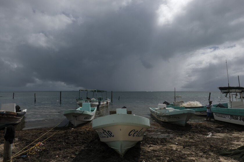 Fishermen secure boats in Cancun, Mexico, ahead of Hurricane Delta.