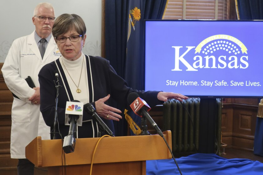 "Kansas Gov. Laura Kelly answers questions about the state's response to the coronavirus pandemic as Dr. Lee Norman, her health secretary, watches behind her, Monday, June 8, 2020, at the Statehouse in Topeka, Kan. Kelly the state's counties ""shouldn't feel pressure"" to lift restrictions further if they're not seeing new cases and new hospitalizations decline. (AP Photo/John Hanna)"