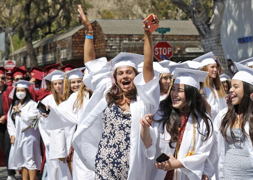 Jessie Rose, center, raises her arms during the Laguna Beach High class of 2021 Procession to Main Beach.
