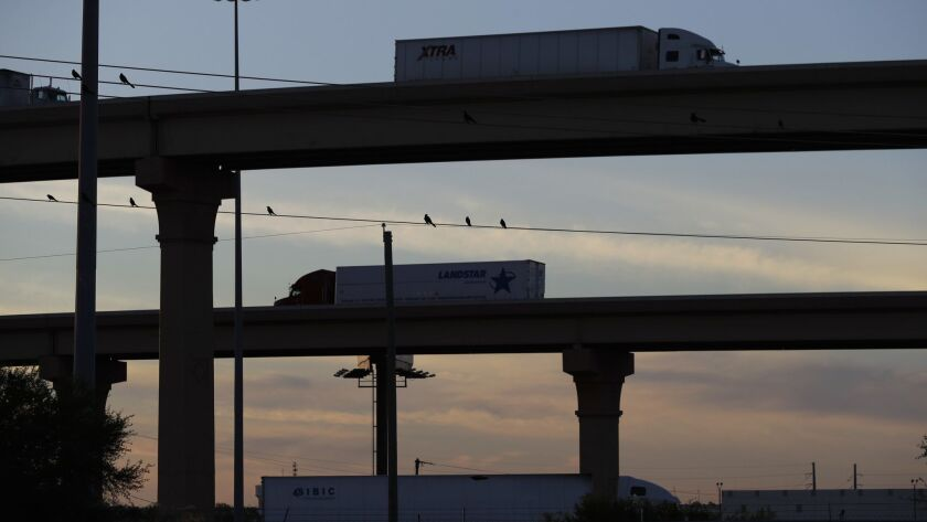 FILE - In this Nov. 21, 2016 photo, trucks travel on an overpass to and from the World Trade Bridge,