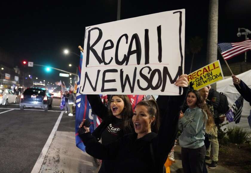 Trump supporters in November shout slogans while carrying a sign calling for a recall on California Gov. Gavin Newsom.