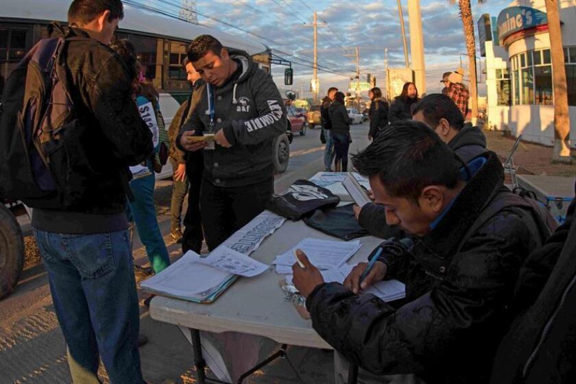 Varias personas que buscan empleo se inscriben para aspirar a las vacantes de una empresa maquiladora en la frontera. EFE/Archivo