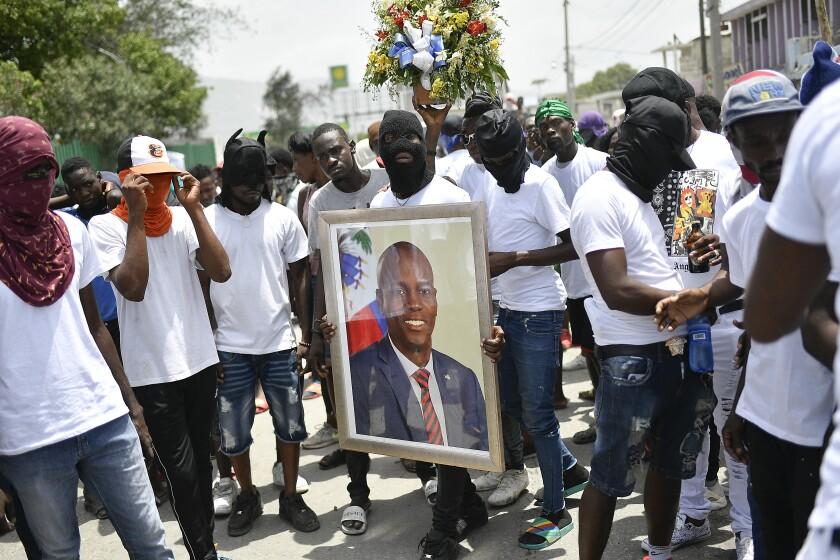 """Miembros de una pandilla encabezada por Jimmy Cherizier, alias Berbecue, un expolicía que encabeza una coalición de pandillas llamada """"Familia G9 y Aliados"""", transportan un retrato del asesinado presidente Jovenel MoÍse durante una marcha efectuada el lunes 26 de julio de 2021 en el vecindario de La Saline en Puerto Príncipe, Haití, para exigir justicia tras el magnicidio. (AP Foto/Matias Delacroix)"""