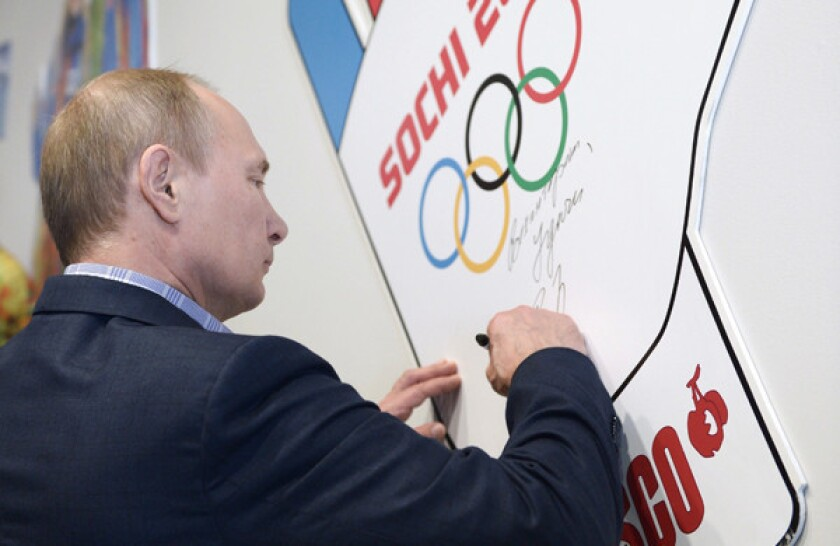 Russian President Vladimir Putin signs his name during a visit to a training center for Winter Olympic Games volunteers in Sochi, Russia, on Saturday. The Black Sea resort city will play host to the 2014 Olympic Games next month.