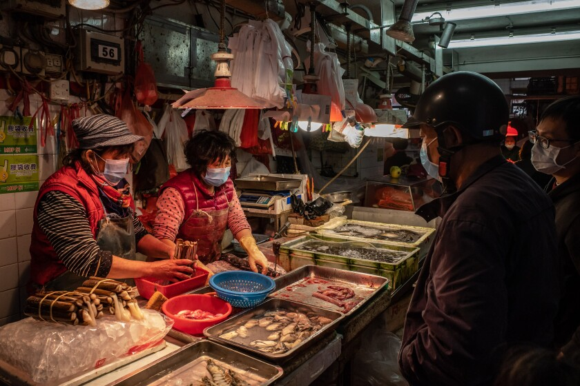 Residents wearing face masks purchase seafood at an open-air market on Jan. 28 in Macao, where at least 10 people have reportedly contracted the coronavirus.