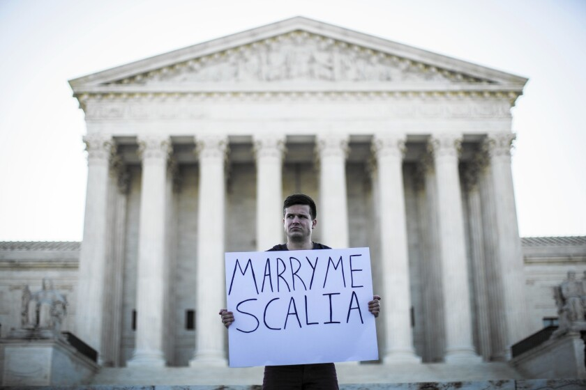 Ryan Aquilina of Washington, D.C., a supporter of same-sex marriage, demonstrates near the Supreme Court on April 28. The court has decided same-sex couples have a right to marry nationwide.