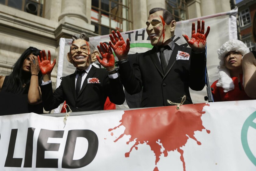 Protesters wearing a former British Prime Minister Tony Blair mask, left, and former U.S. President George W. Bush mask pose for the media outside the Queen Elizabeth II Conference Centre in London, shortly before the publication of the Chilcot report into the Iraq war, Wednesday, July 6, 2016. The