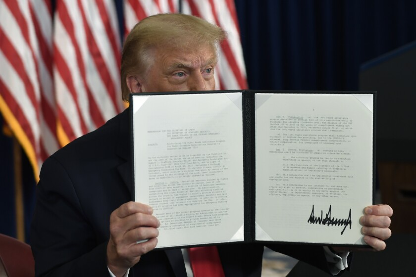President Trump holds up a signed executive order during a news conference in Bedminster, N.J., on Aug. 8.