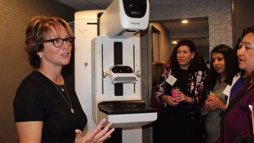 Marsha Friend-Berkson explains the mammography process and technology to some symposium attendees.