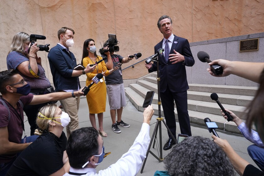 California Gov. Gavin Newsom responds to a question while meeting with reporters