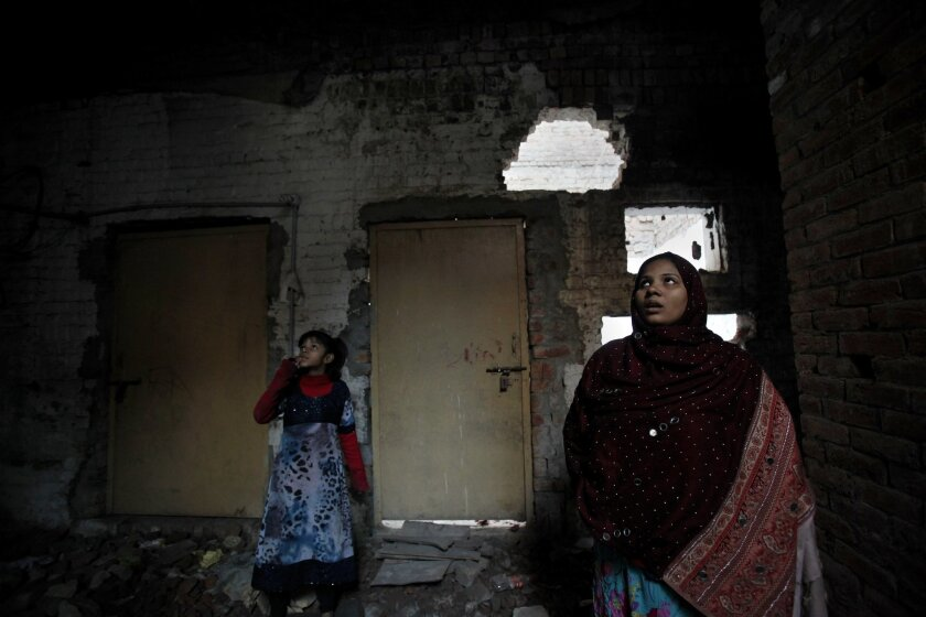 In this Saturday, Jan. 11, 2014, photo,  Pakistani Christian, Nomi Shahid and her daughter Aliza, stand at their house, which was torched by radical Muslim's mob last March, in Lahore. Pakistan's blasphemy law has become a potent weapon in the arsenal of Muslim extremists, who use it against adhere