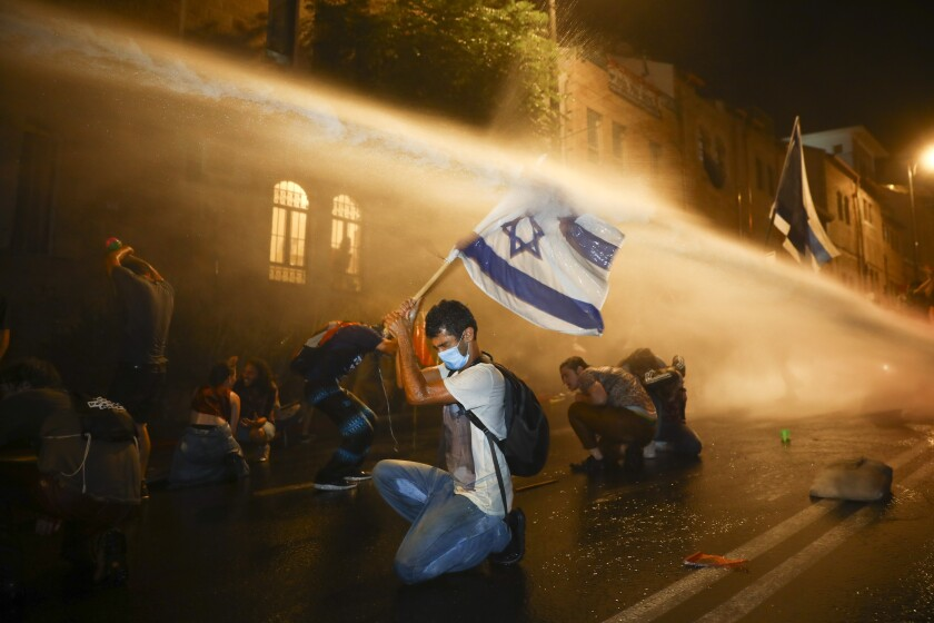 Protesters in Jerusalem are targeted with a police water cannon earlier this month.