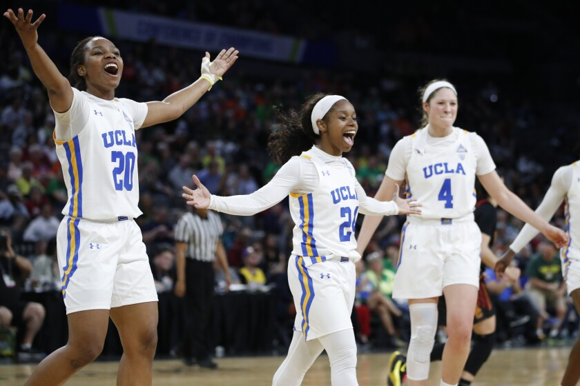 UCLA's Charisma Osborne, left, Japreece Dean, center, and Lindsey Corsaro celebrate after a play against USC during the second half in the quarterfinal round of the Pac-12 women's tournament on March 6 in Las Vegas.