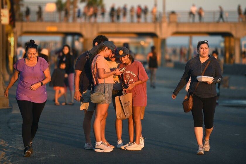 HUNTINGTON BEACH, CALIFORNIA JULY 17, 2020-Pedestrians walk along the strand in Huntington Beach as Orange County deals with a surge in the cornavirus. (Wally Skalij/Los Angeles Times)