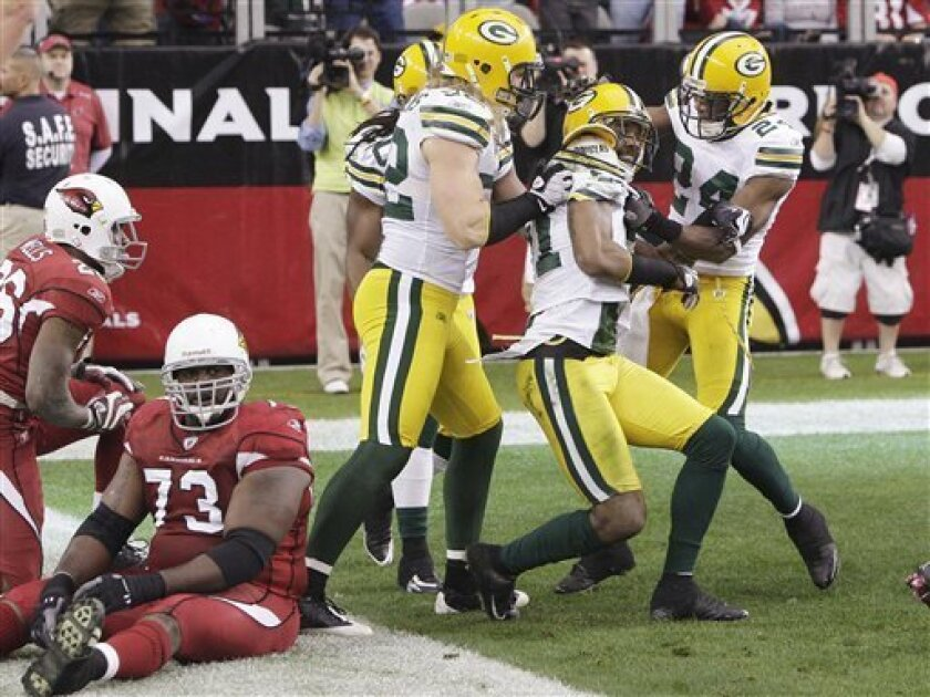 Green Bay Packers' Charles Woodson, second from right, celebrates his interception return for a touchdown with teammates Jarrett Bush (24) and Clay Matthews, front left, and Atari Bigby, back, as Arizona Cardinals' Jeremy Bridges (73) sits on the ground near teammate Beanie Wells, left, in the second quarter of an NFL football game Sunday, Jan. 3, 2010, in Glendale, Ariz. The Packers defeated the Cardinals 33-7. (AP Photo/Ross D. Franklin)