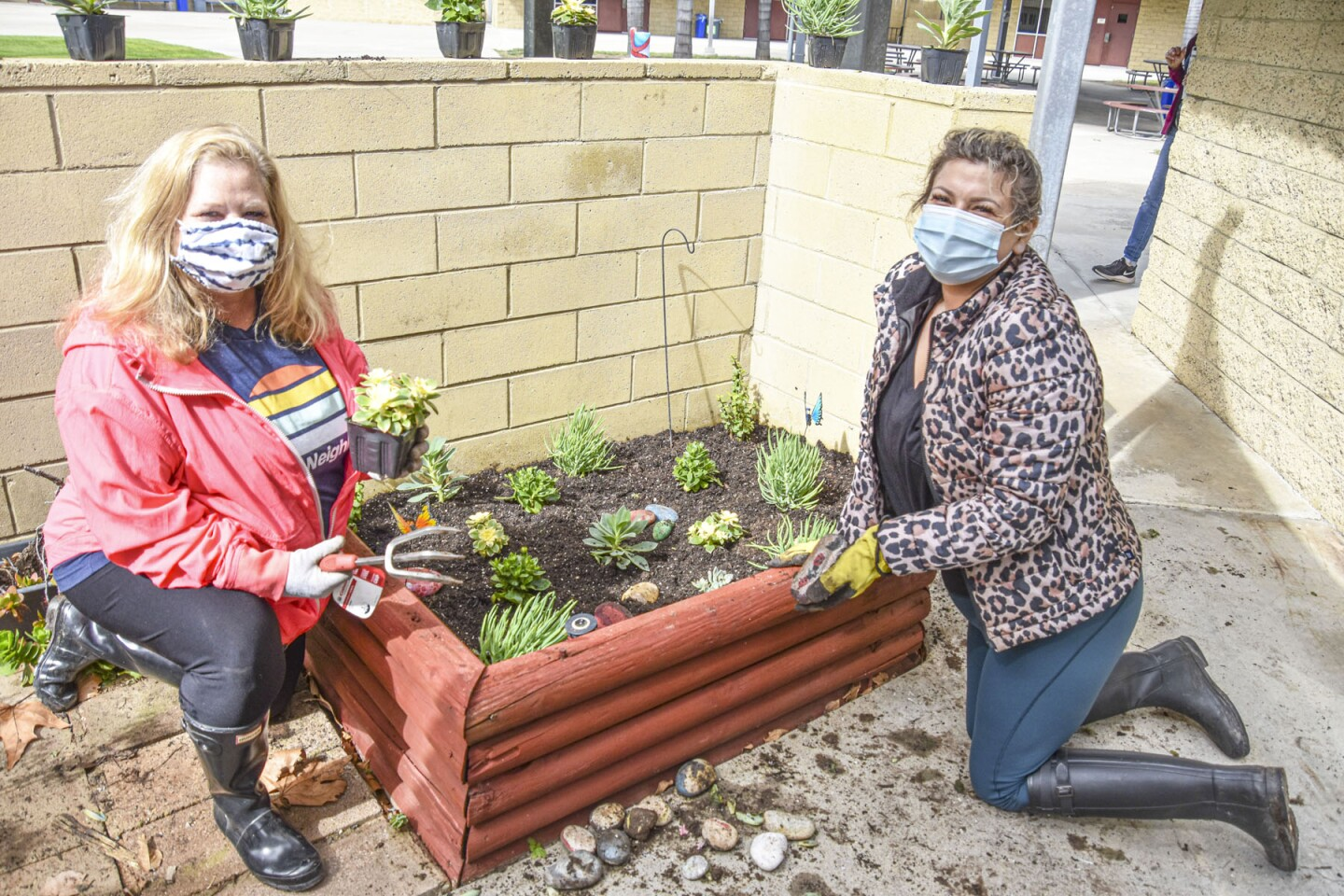 Monda Forrestal and Jessica Norris planting succulents at Abraxas High School.