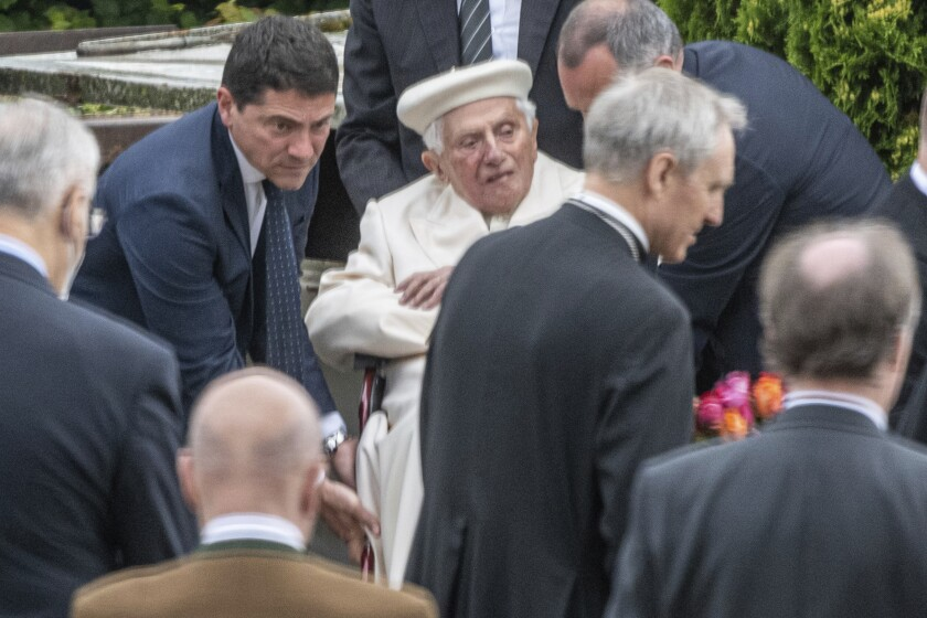 """Emeritus Pope Benedict XVI is wheeled in his wheelchair as he visits the grave of his parents and sister at the Ziegetsdorf cemetery near Regensburg, Germany, Saturday, June 20, 2020. The Vatican says Emeritus Pope Benedict is in Germany to be with his brother, who is in poor health. Benedict on Thursday arrived in Regensburg, Germany, where his brother, the Rev. Georg Ratzinger, lives, and where """"he will spend the necessary time,"""" the Vatican said in a statement. (Armin Weigel/dpa via AP)"""