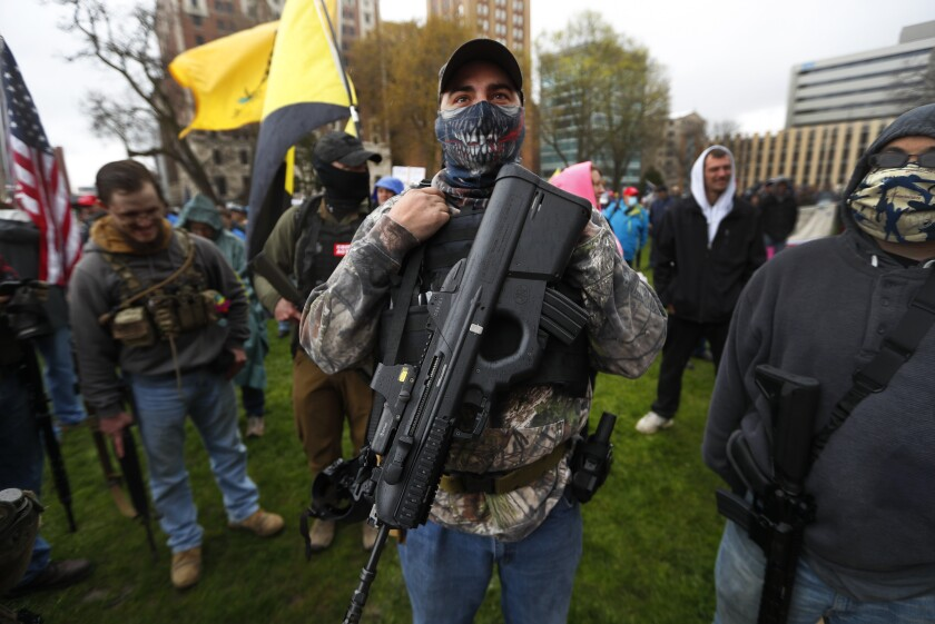 "A protester carries his rifle at the State Capitol in Lansing on April 30. President Trump urged Michigan Gov. Gretchen Whitmer to ""make a deal"" with the protesters over the state's lockdown rules."