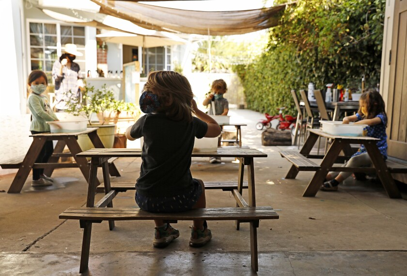 Children do activities outside at separate tables at Voyages Preschool in Los Angeles.