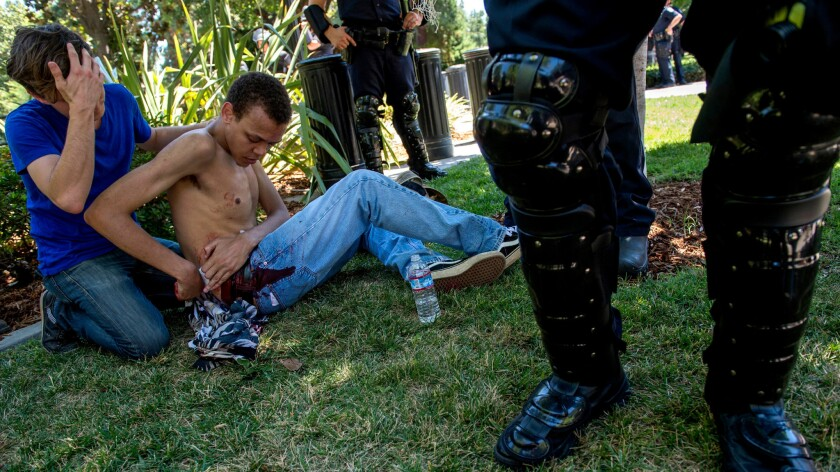 A 23-year-old Sacramento resident waits for medics after being stabbed at Sunday's rally.