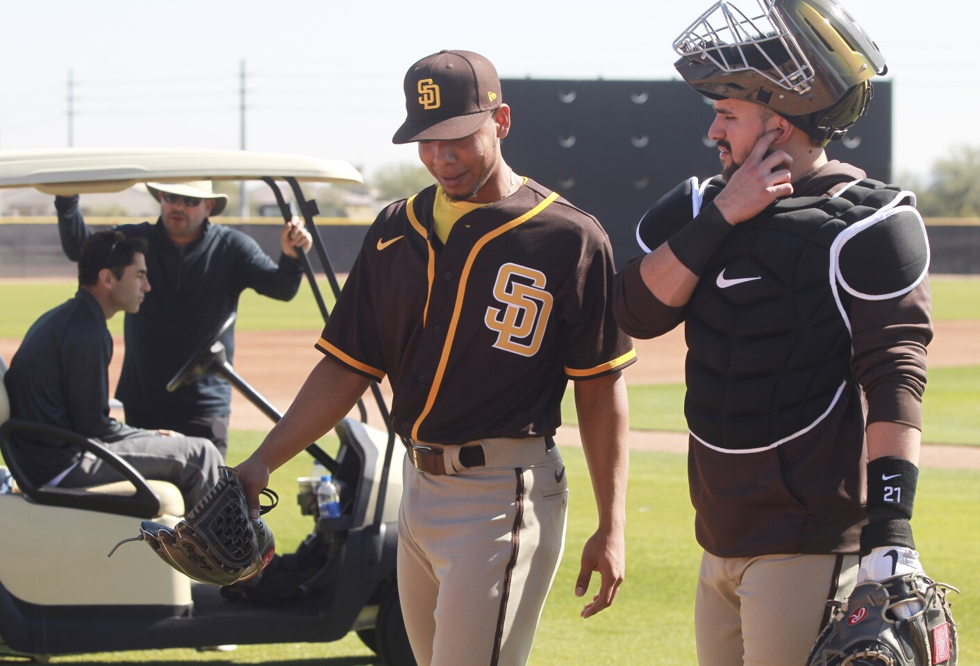 Padres pitcher Luis Patiño walks off the field with catcher Luis Torrens after Patiño threw pitches while Padres General Manager A.J. Preller, sitting in cart, left, watched during Padres spring training at the Peoria Sports Complex on Thursday, February 13, 2020 in Peoria, Arizona.