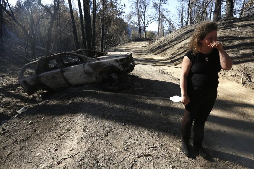 Charlotte Scott stands near her charred Volvo in Redwood Valley.