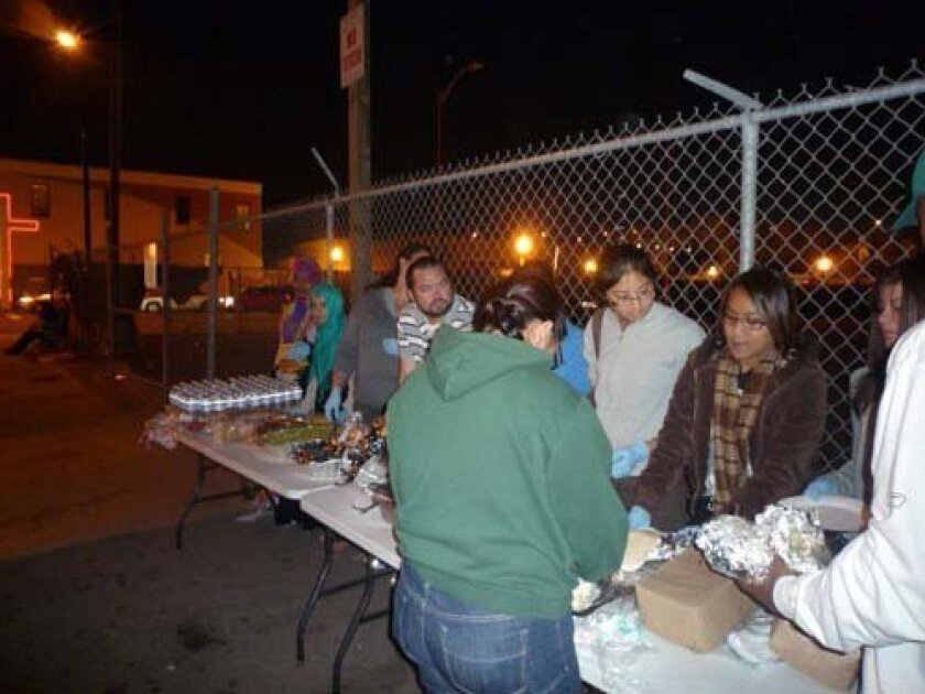 Khoban N. Ludin, second from left, vice president of UCSD's Muslim Student Association, and other club members feed the homeless on downtown streets. COURTESY