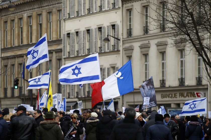 Pro-Israel demonstrators hold Israeli and French flags during a gathering in front of Israel embassy in Paris on Jan. 15, 2017.