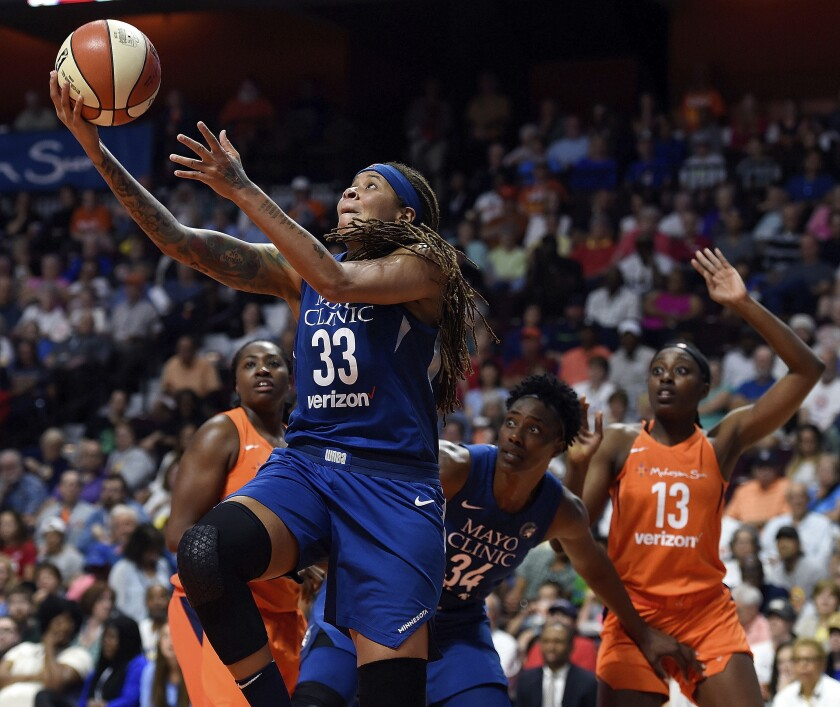 FILE - In this June 9, 2018, file photo, Minnesota Lynx guard Seimone Augustus (33) uses a screen from teammate Sylvia Fowles (34) to get a clear drive to the basket against the Connecticut Sun during the first half of a WNBA basketball game in Uncasville, Conn. Seimone Augustus has retired from playing and will be an assistant coach for the Los Angeles Sparks, the team announced Thursday, May 13, 2021. (Sean D. Elliot/The Day via AP, File)