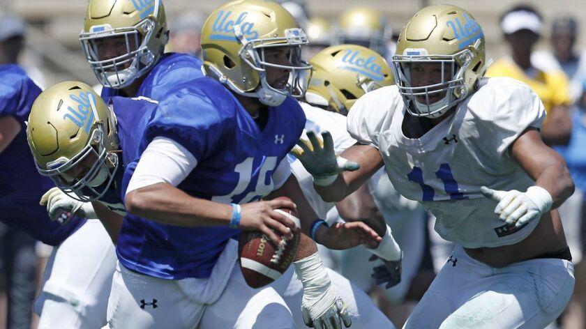 LOS ANGELES, CALIF. - APR. 21, 2018. UCLA quarterback Devon Modster gets pressured by defensive bac