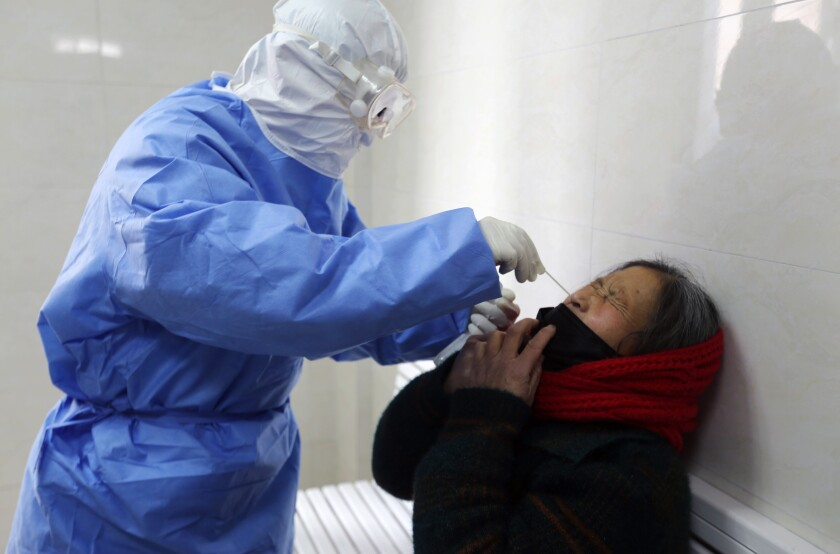 A doctor takes a swab from a woman to test for the COVID-19 virus at a fever clinic in Yinan county in eastern China's Shandong province on Wednesday, Feb. 12, 2020. China on Wednesday reported another drop in the number of new cases of a viral infection and 97 more deaths, pushing the total dead past 1,100 as postal services worldwide said delivery was being affected by the cancellation of many flights to China. (Chinatopix Via AP)