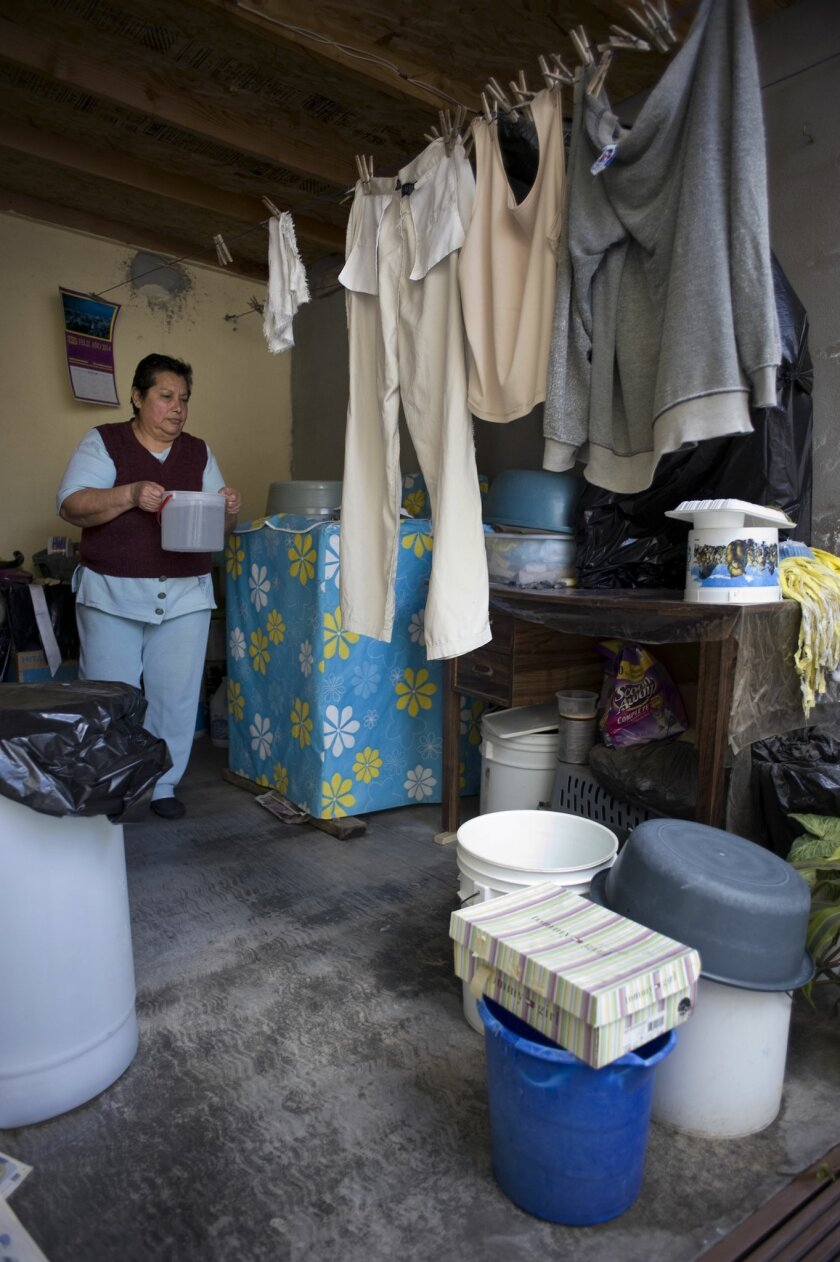 Ensenada resident Minerva Altamirano stores water in her back patio for the days when her taps are dry.