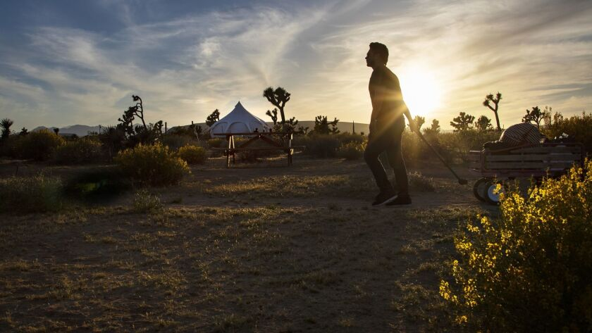 Jose Sanchez-Castro of Pasadena pulls his luggage in a wagon along a dirt trail upon arriving at Lazy Sky Retreat in Joshua Tree.