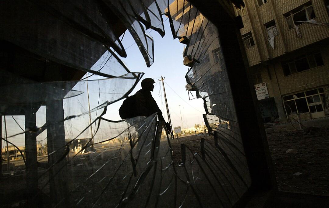 یک تفنگدار دریایی ایستاده است ، از سوراخی در یک شیشه شکسته دیده می شود